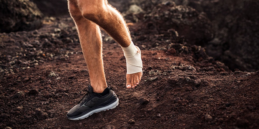 Man hiking with wrapped ankle