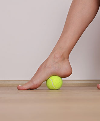 Close up of foot rolling tennis ball