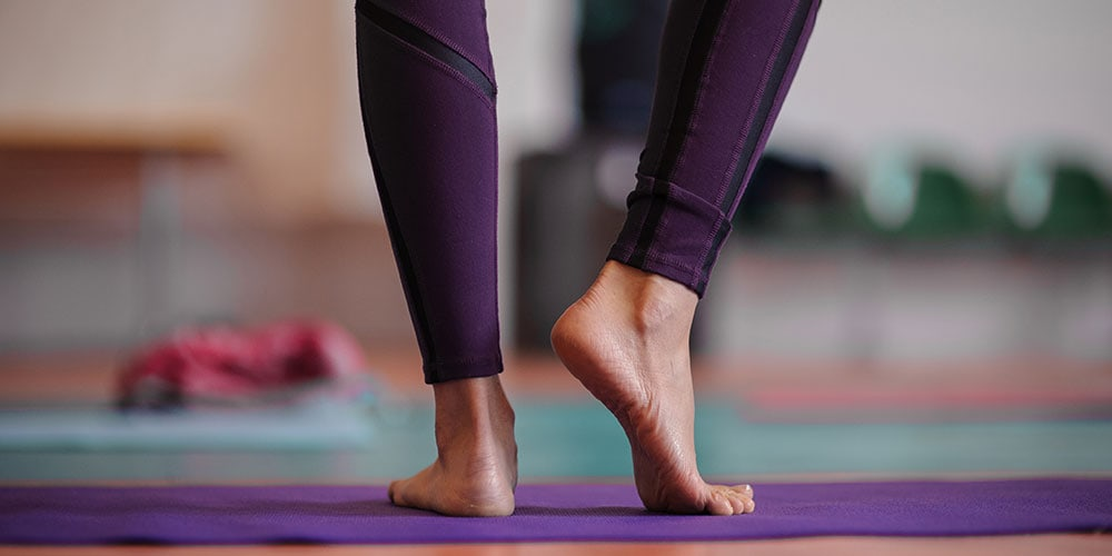 Close up of woman's legs standing on yoga mat